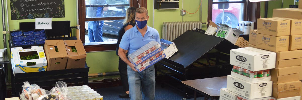 Mark Politte (masked), helping store boxes of food at Bar Harbor Food Pantry