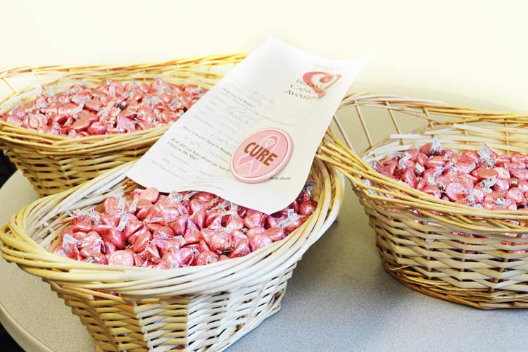 Baskets of pink-wrapped Hershey Kisses