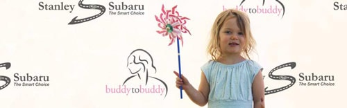 A young child holding a pinwheel in front of a backlit Buddy to Buddy and Stanley Subaru banner at the Pink Tulip Festival