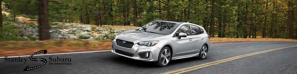 2016 Impreza zipping down a road through the forest