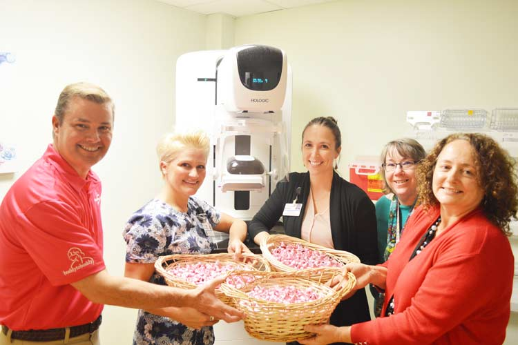 Stanley Subaru and Breast Health Clinic staff in front of the 3-D mammography machine, holding baskets of pink-wrapped Hershey Kisses