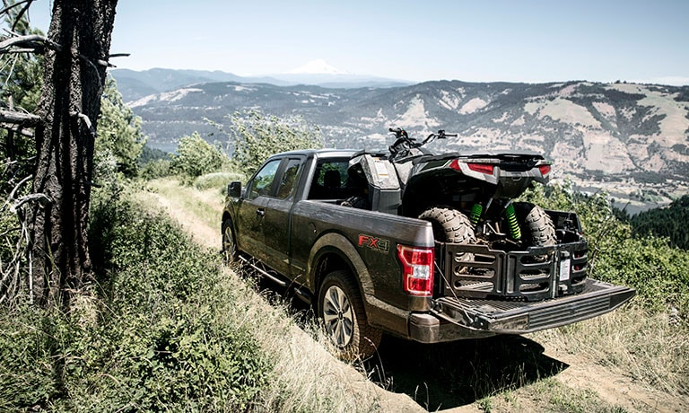 2019 Ford F-150 towing atv out in field