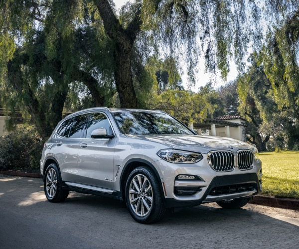 New BMW X3 driving down a town road