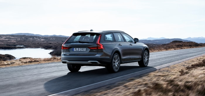New Volvo V90 Cross Country driving away down a road