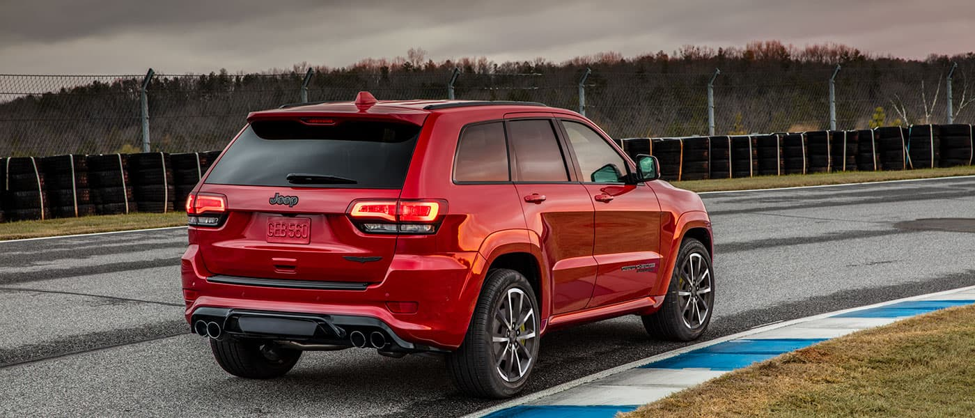 Red 2019 Jeep Grand Cherokee driving on racetrack