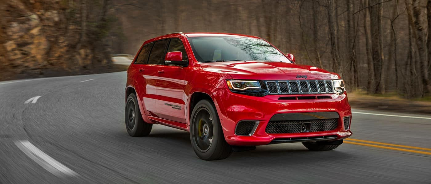 Red 2019 Jeep Grand Cherokee driving down road