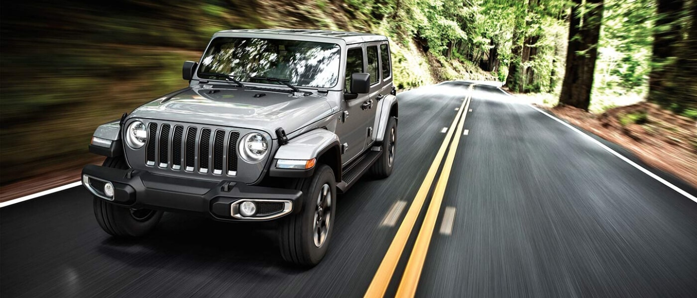 2019 Jeep Wrangler driving on road in forrest