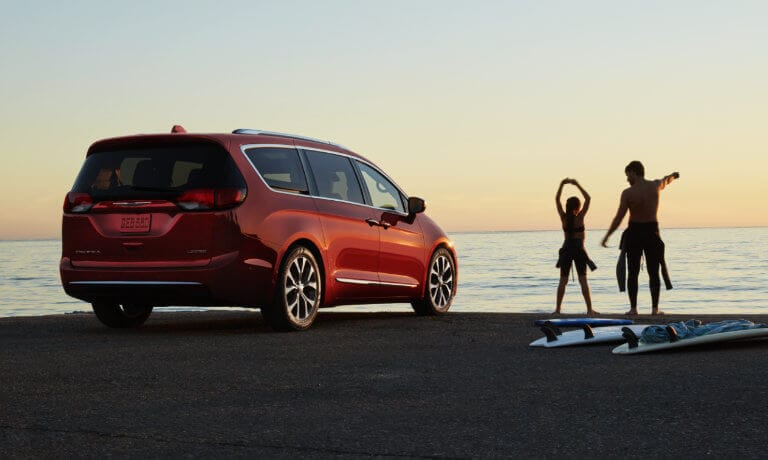 2019 Chrysler Pacifica parked on beach with couple