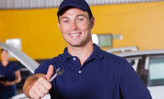 Smiling auto collision repair technician with tool in hand