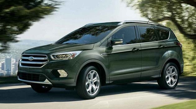 Green 2019 Ford Escape driving through a park with a cityscape background