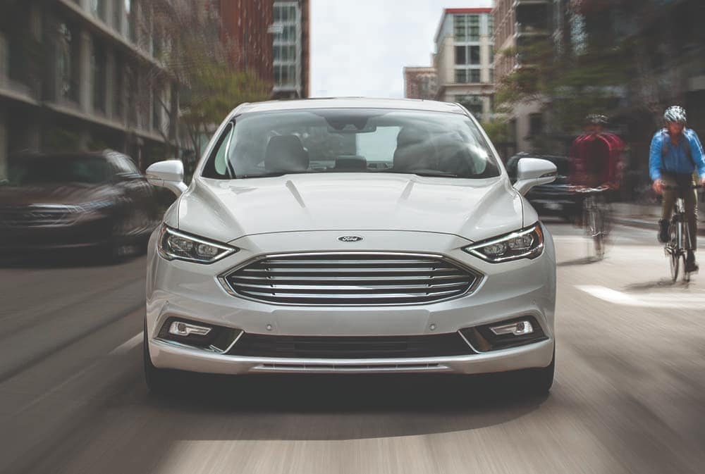 2019 Ford Fusion driving down street past bikers