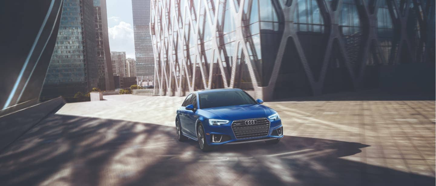 2019 Blue Audi A4 Driving Past a Building