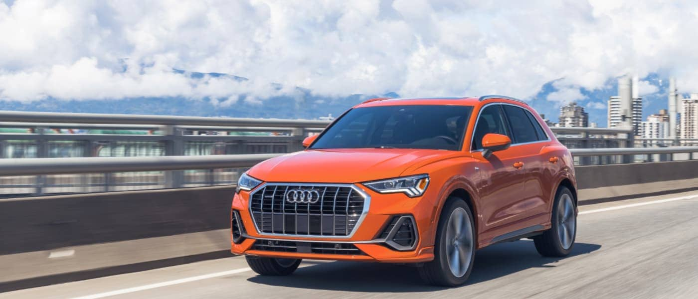 2020 Orange Audi Q3 Driving over a Bridge past the City