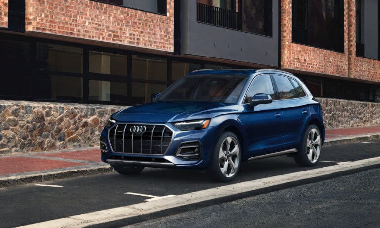 2021 Audi Q5 parked along city brick sidewalk and road