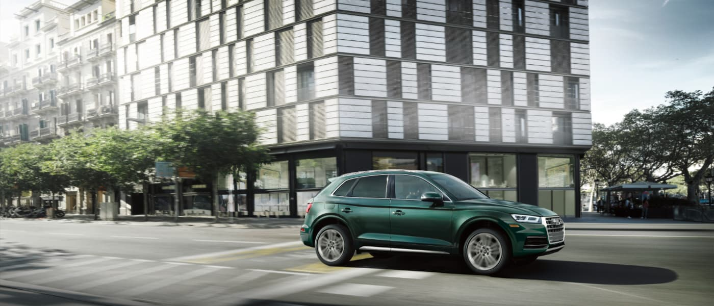 2019 Green Audi Q5 Driving by a Building