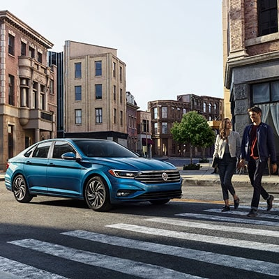 A blue Volkswagen stopped at a crosswalk