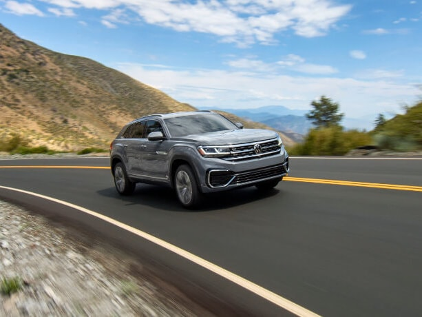A silver 2020 VW Atlas Cross Sport driving down a coast