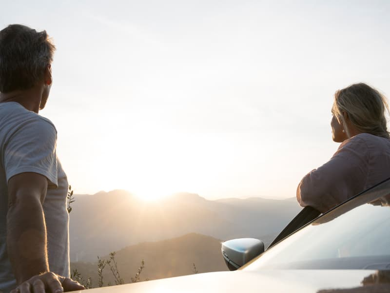 Two people looking at a sunrise over the mountains by their 2020 VW Passat