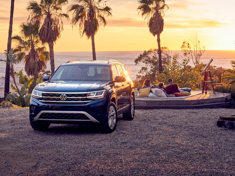 A blue 2021 VW Atlas parked by a beach at sunset
