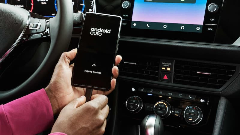 A person pluging their phone in with android auto