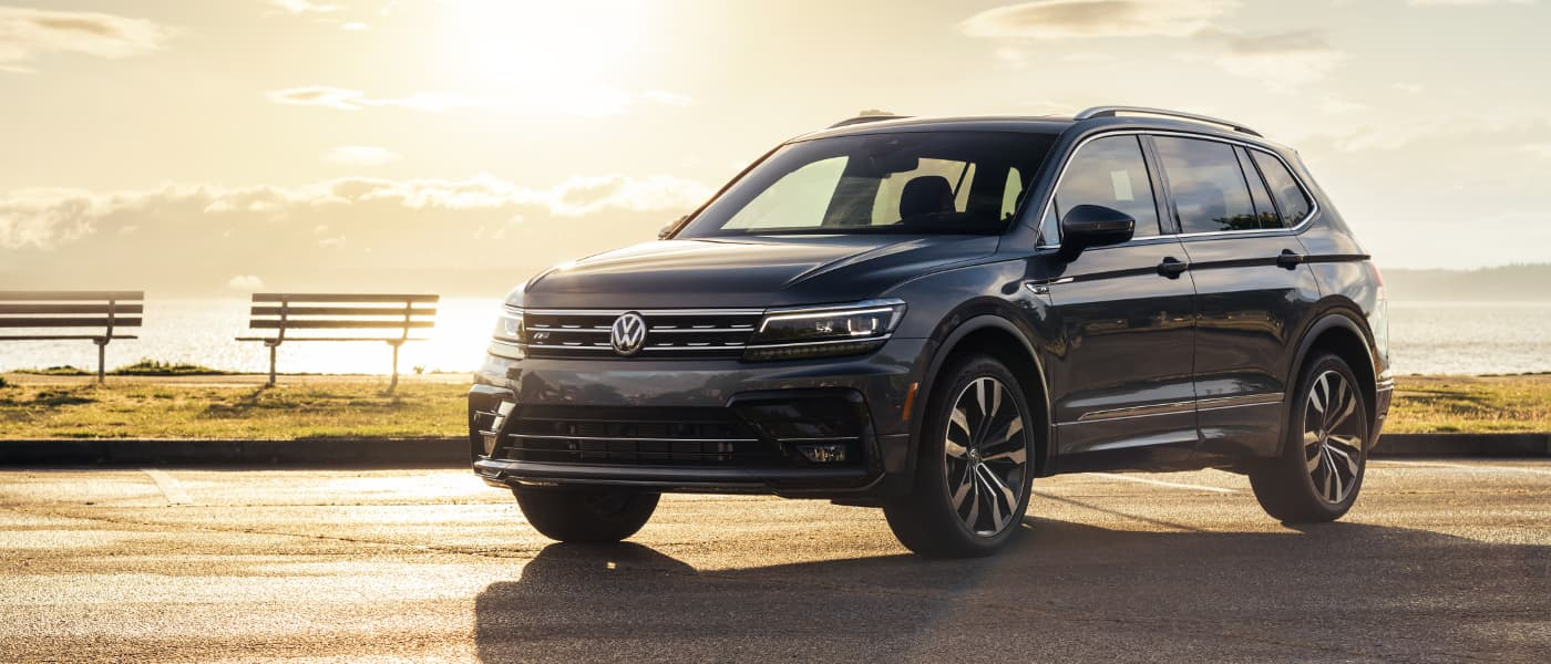 A black 2020 VW Tiguan parked in front of a sunset