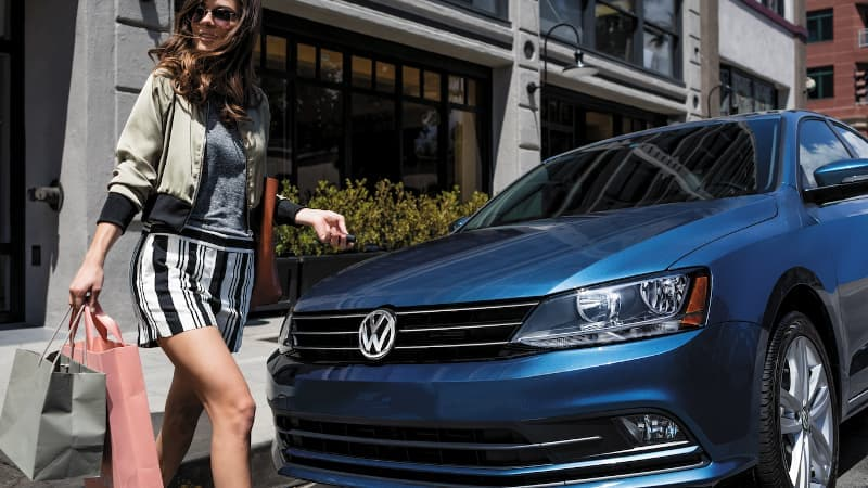 A woman walking to her 2017 VW Jetta
