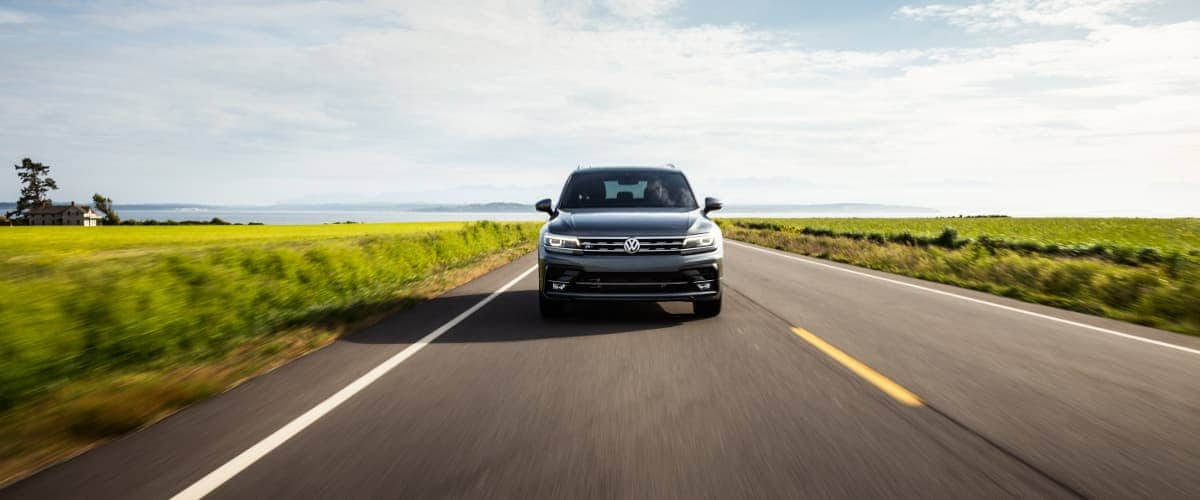 A black 2019 Volkswagen Tiguan driving down an open country road