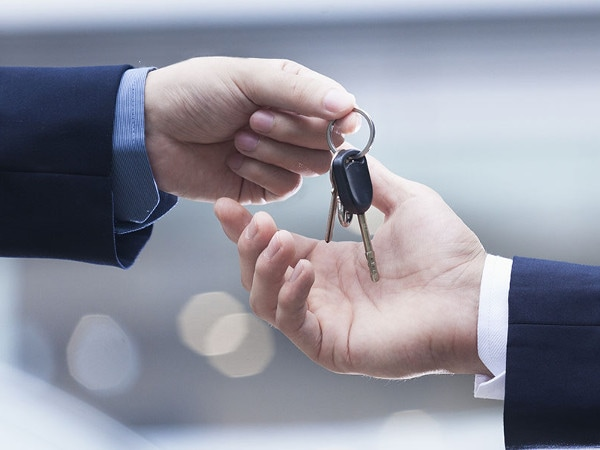 One person handing the keys to a car to another person