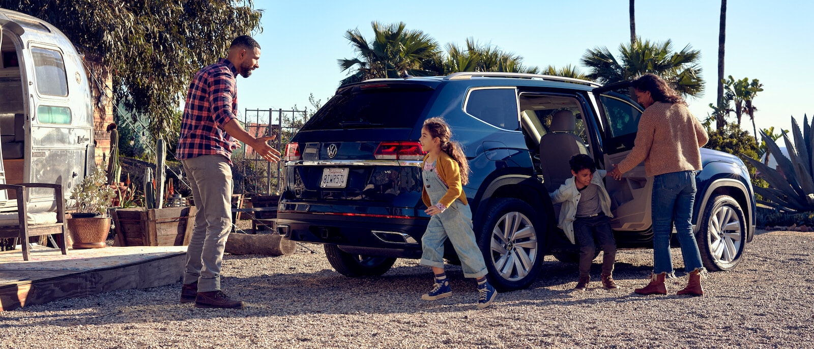 Kids running out of their 2021 Blue VW Atlas to their dad