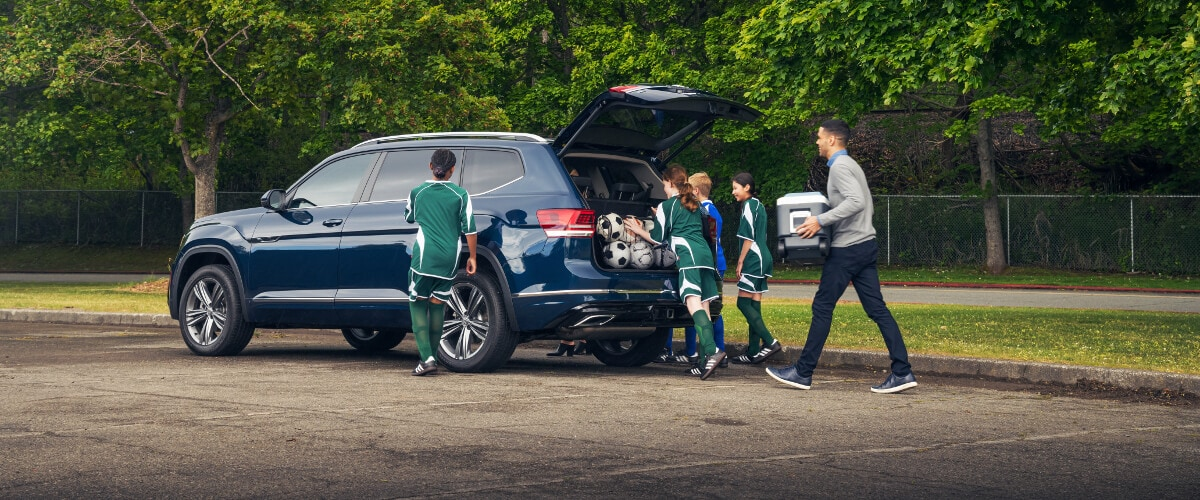 A group of kids putting soccer equipment into the back of a Volkswagen Atlas