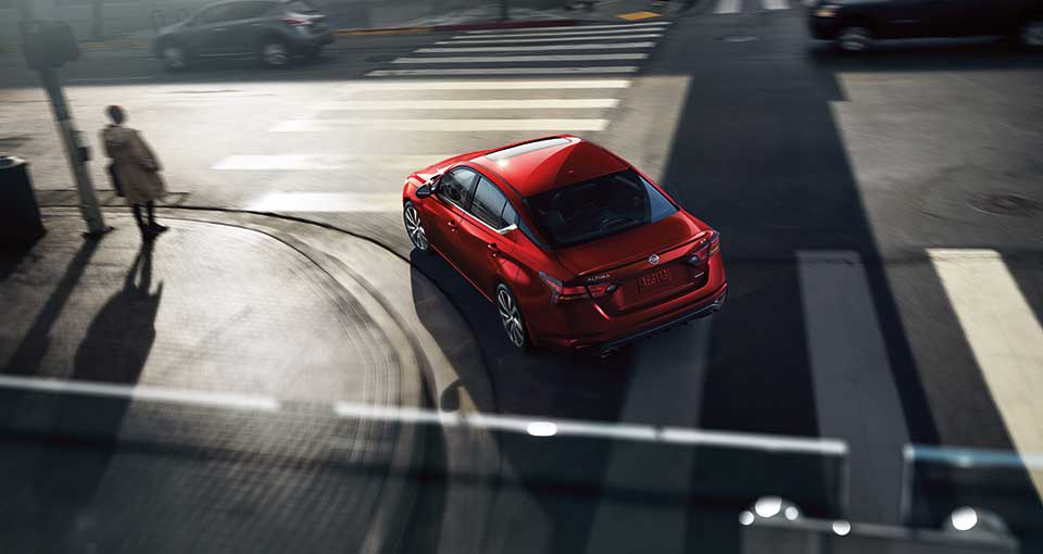 A red 2019 Nissan Altima turning a corner