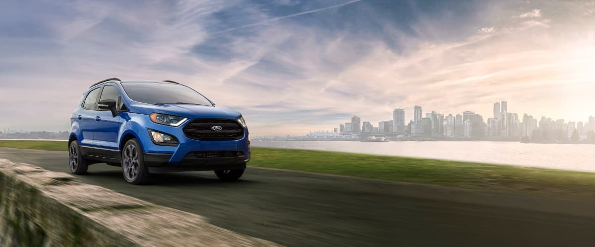 A blue 2019 Ford EcoSport driving past a city skyline
