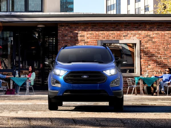 A blue 2019 Ford EcoSport parked in front of a brick building