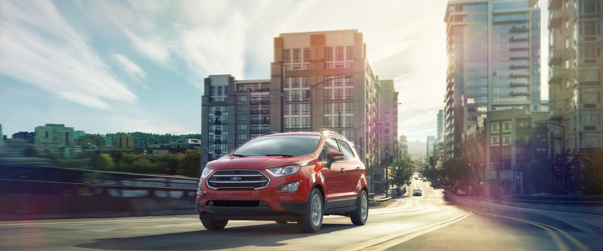 A red 2019 Ford EcoSport driving through a city
