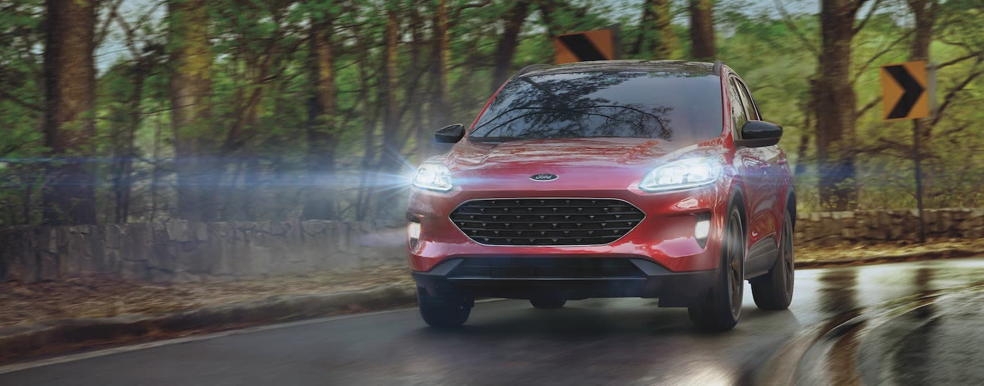 A red 2021 Ford Escape Hybrid is driving on a road in the rain.