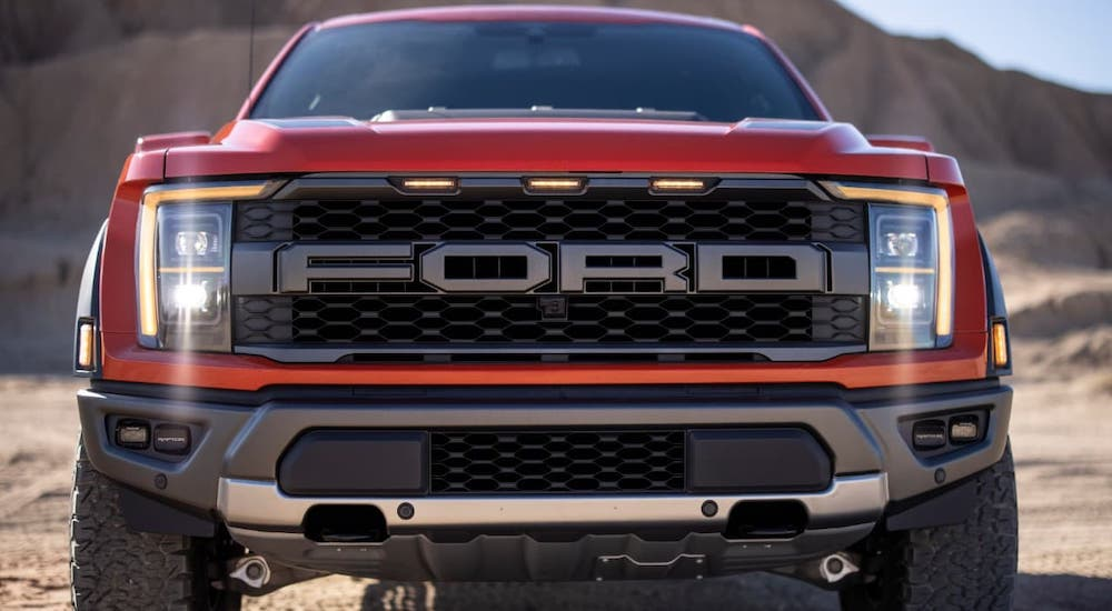 A red 2021 Ford F-150 Raptor is shown from the front against piles of sand.
