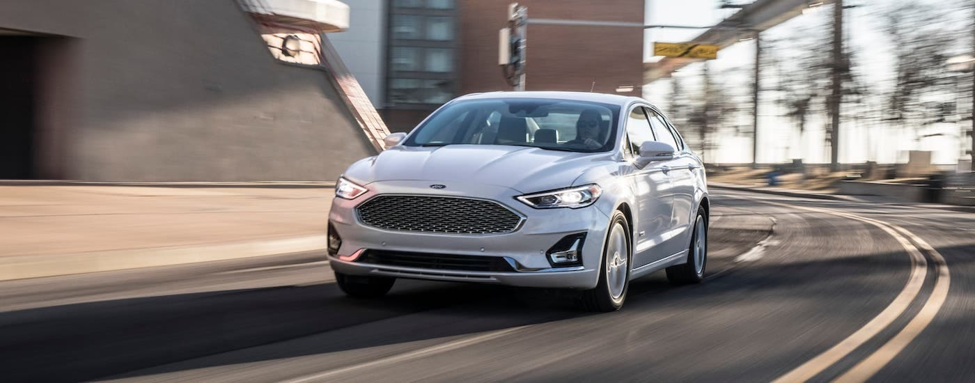 A white 2021 Ford Fusion is driving on a city street after leaving a Louisville Ford dealer.