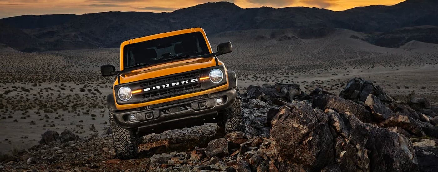 An orange 2021 Ford Bronco is shown from the front climbing over rocks in a desert.