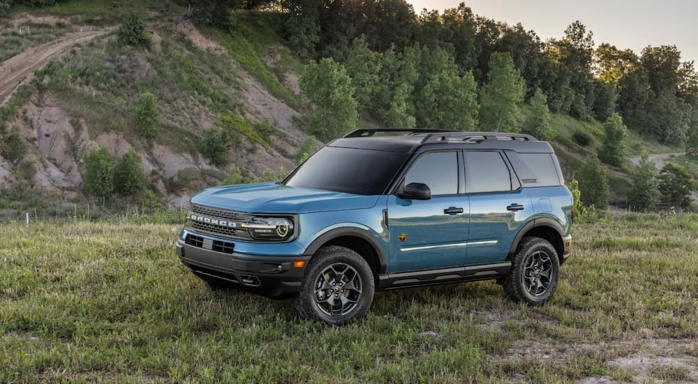 A blue 2021 Ford Bronco Sport is shown from the side parked in front of a hill.