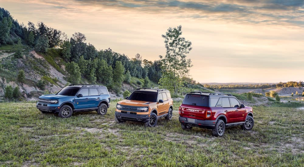 A blue, a yellow, and a red 2021 Ford Bronco Sport are shown parked on the grass.