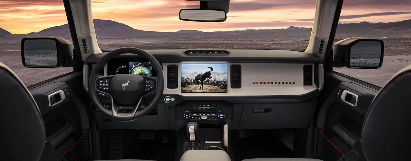 The gray and black dashboard of a 2021 Ford Bronco is shown overlooking a desert at sunset.