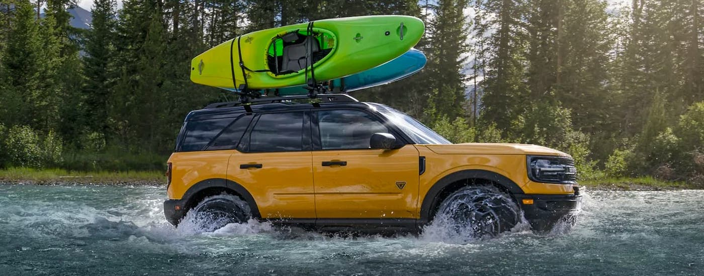 A yellow 2021 Ford Bronco Sport with kayaks on the roof is driving through a river.