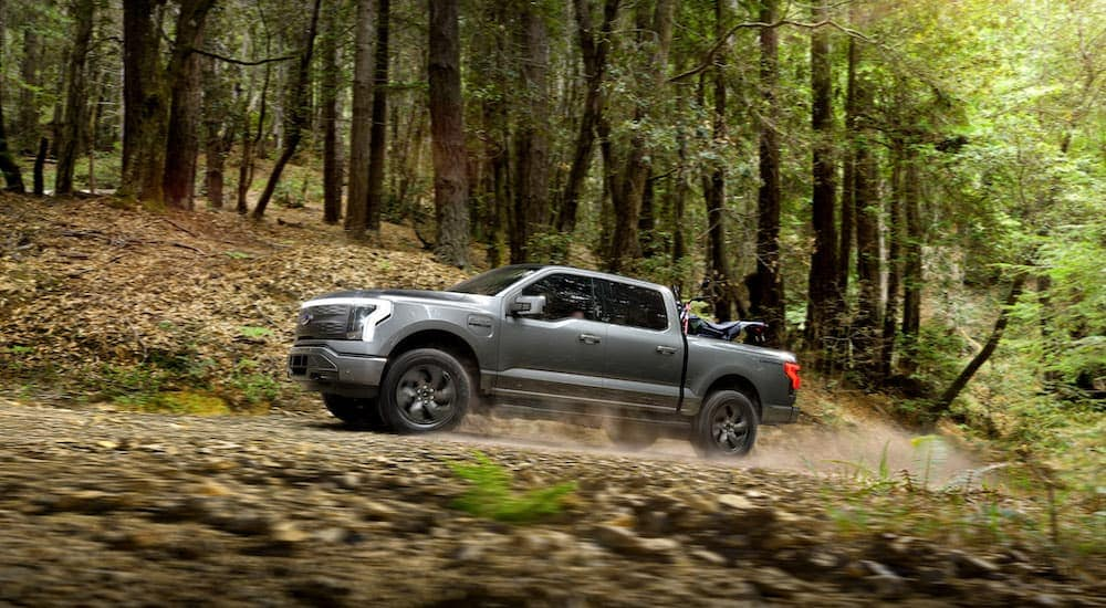 A popular Ford electric vehicle, a grey 2022 Ford F-150 Lightning Lariat, is shown from the side driving through the woods.