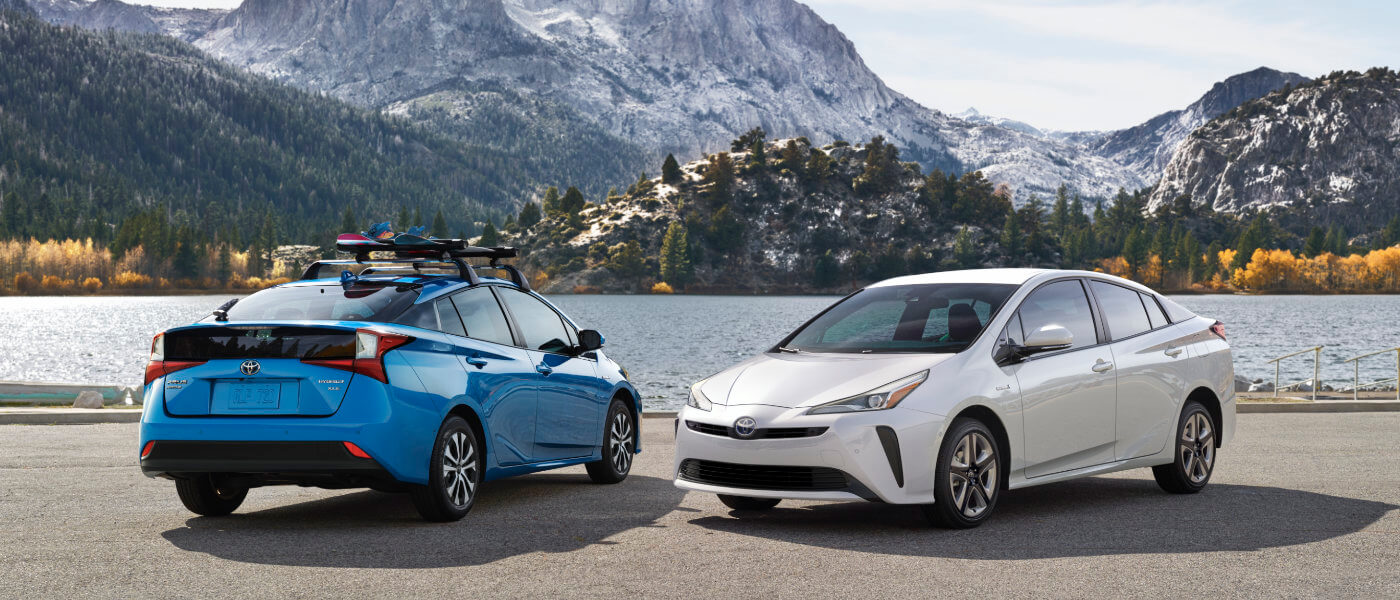 two 2020 toyota Prius parked in a parkinglot next to a lake with mountians in the backfground