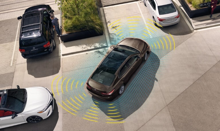 2020 Toyota Camry parking in parking lot witha visual of the saftey sensors