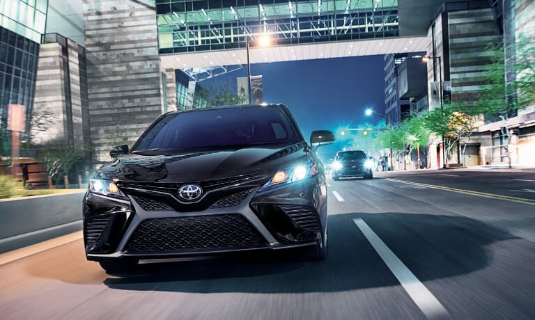 2020 Toyota Camry in black driving at night head on in a city