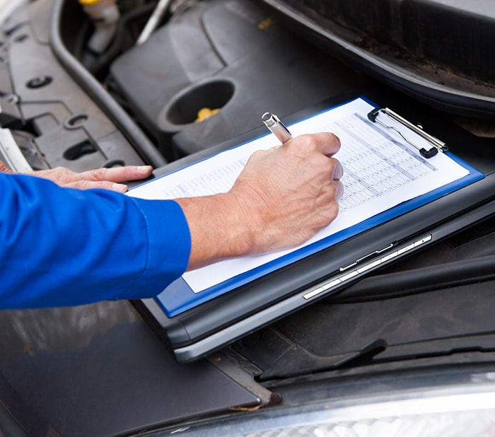 Mechanic filling out vehicle inspection checklist