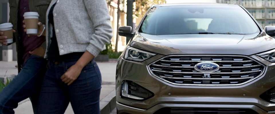 Two people walking in front of a 2019 Ford Edge