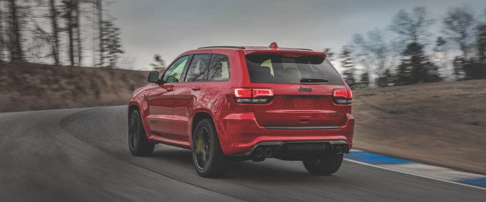 A red 2019 Jeep Grand Cherokee driving away