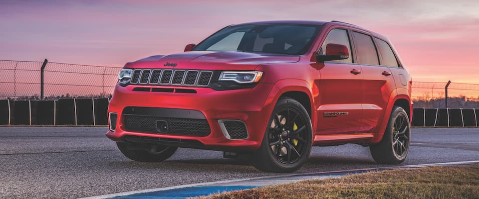 A red 2019 Jeep Grand Cherokee parked on a track at sunset